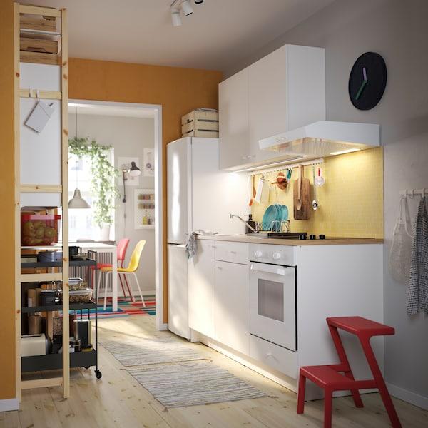Prikaz KNOXHULT bijele kuhinje, crvenog pomoćnog stolca, regala od borovine, crnih kolica i šarenih kuhinjskih stolica.