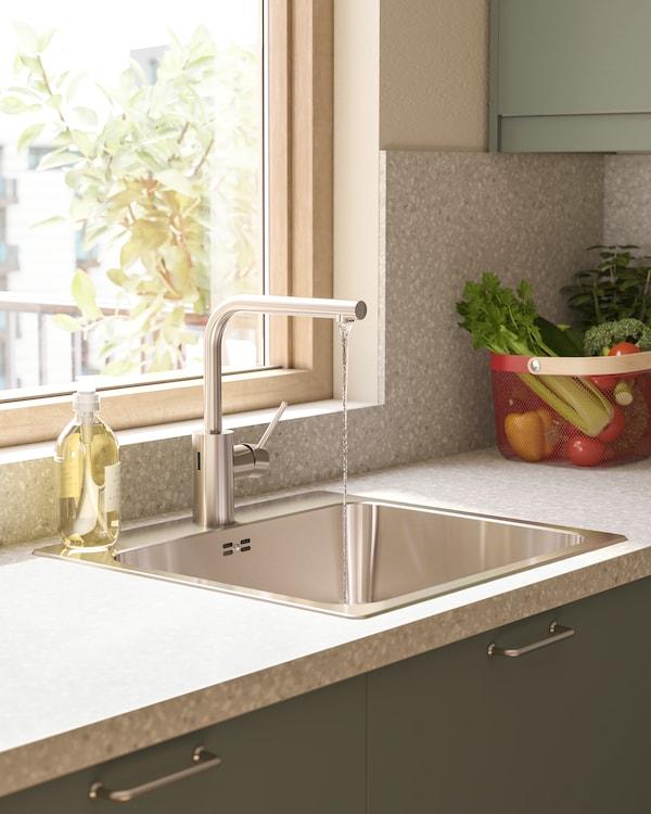 Prikaz kuhinje s miješalicom za vodu boje čelika koja ima sa strane ima senzor. Voda teče iz miješalice.