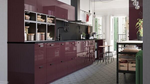 Prikaz kuhinje visokog sjaja tamnocrvene boje, poda s uzorkom šesterokuta i žarulja bez sjenila koje vise sa stropa.