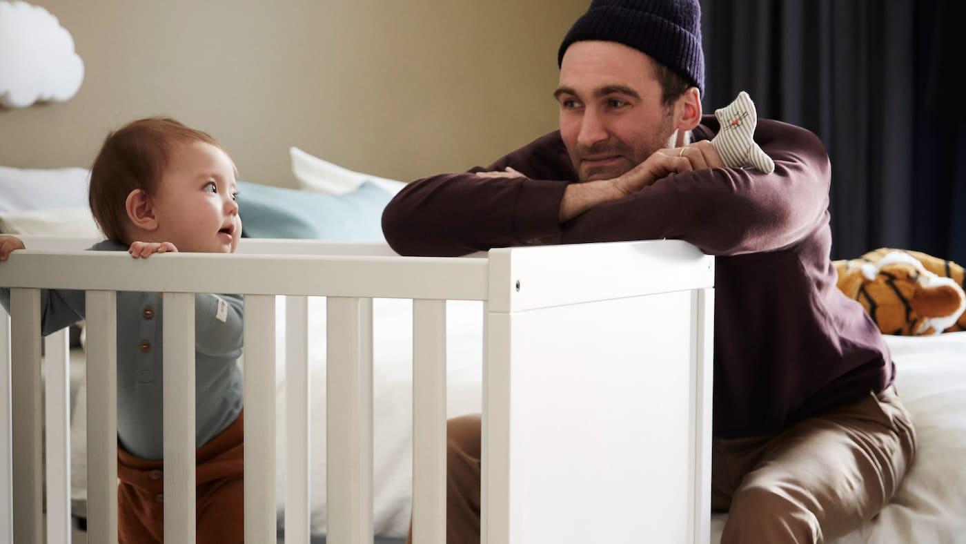 Prikaz oca kako se uz pomoć male drvene igračke igra s djetetom koje stoji u bijelom krevetiću i drži se za ogradu.