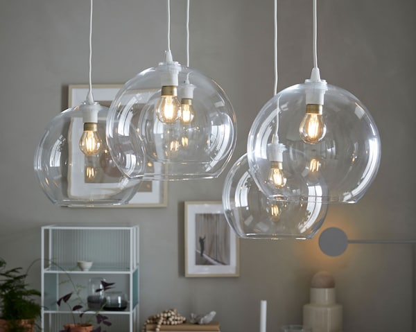 Prikaz pet IKEA JAKOBSBYN sjenila za visilice okrugla oblika od prozirnog stakla kroz koja se vide žarulje.