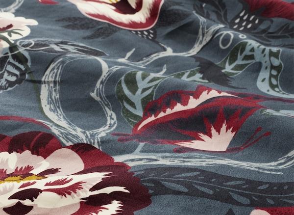Prim-plan cu lenjerie de pat albastră și roșie, cu flori.
