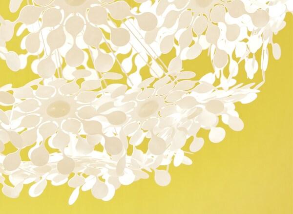 Prim plan cu o lampă cu flori decupate albe pe fundal galben.