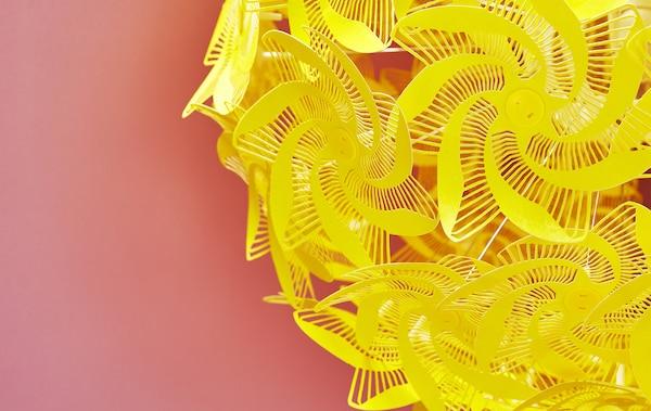Prim plan cu o lampă cu forme decupate galbene pe fundal roșu.