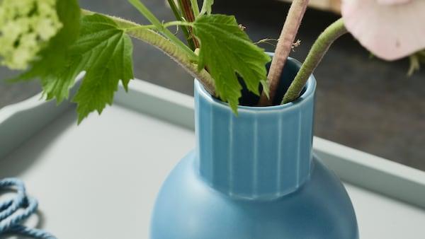 Prim-plan cu o vază OMFÅNG albastră așezată pe o masă lipită de perete pe care se află și ghivece cu plante verzi.