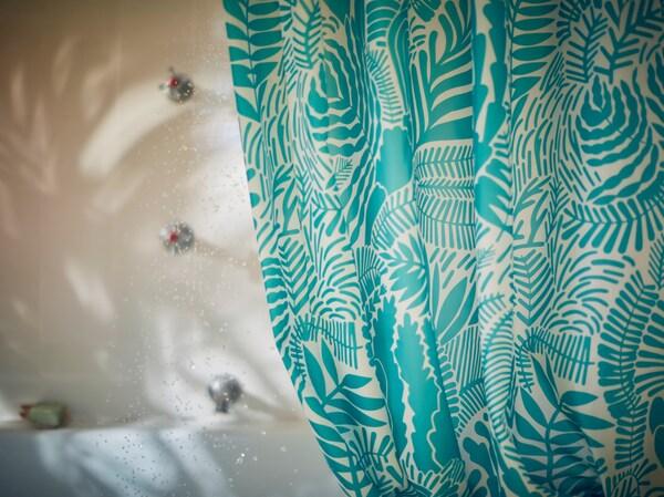 Primeiro plano da cortina de ducha GATKAMOMILL co seu divertido e frondoso estampado branco e turquesa nunha bañeira.