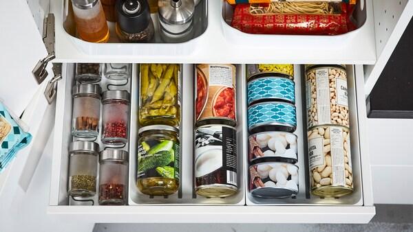 Primeiro plano dun caixón aberto con latas e especias organizadas cos divisores VARIERA.