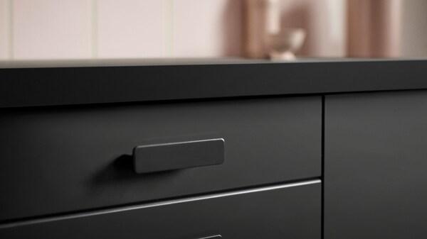 Primer plano de los frentes de cocina KUNGSBACKA de IKEA en negro, fabricados con madera y botellas de plástico PET recicladas.