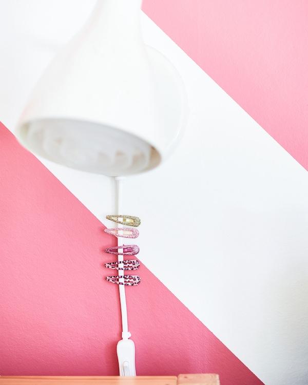 Primer plano de una lámpara de lectura blanca montada en la pared con horquillas en el cable para que sea más fácil de alcanzar.
