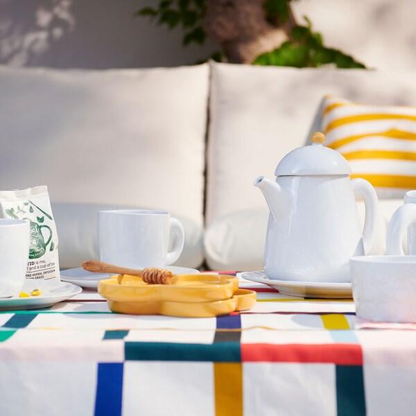 Primer plano de una mesa con una tetera SOMMAR 2019 en loza blanca junto con una taza, un plato y dos platitos amarillos.