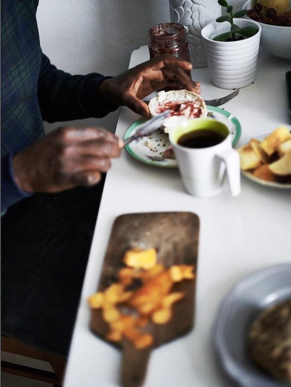 Primer plano de una persona que unta mermelada en un trozo de pan en una mesa con café y algo de comida.