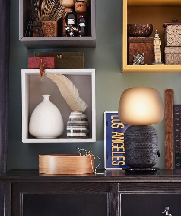 Príručný stolík s lampou s reproduktorom Wi-Fi. Dekoratívne úložné priestory v malých skrinkách na stene nad ním.