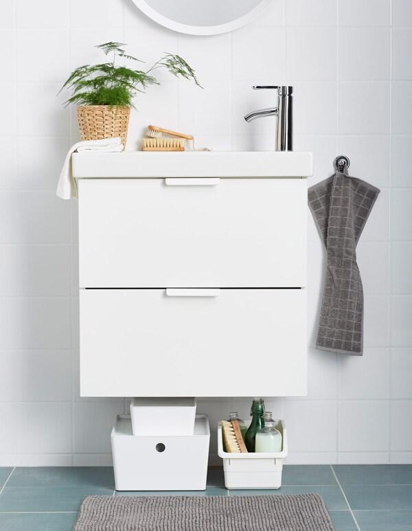 Produits nettoyants placés dans des boîtes plastique déposées sous le meuble-lavabo.