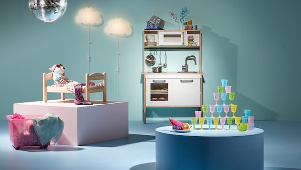 Produkter fra DUKTIG serien står opstillet på et lyseblåt gulv. Der er en dukkeseng af træ og et legekomfur samt forskellige små dele såsom drikkeglas af plast i forskellige farver.