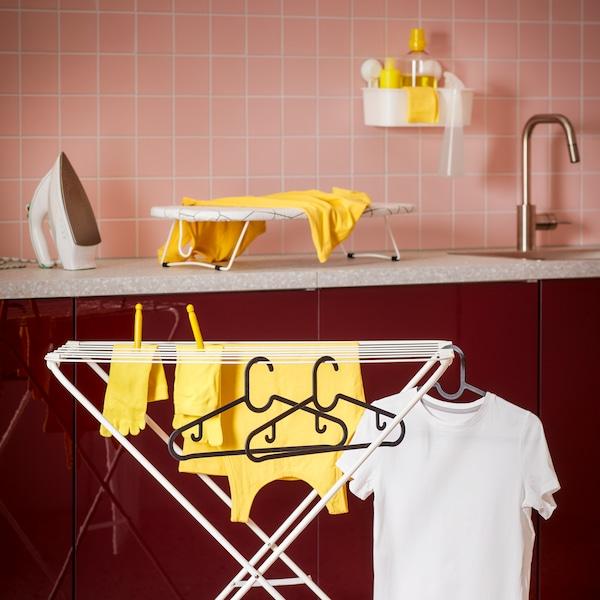 Prostor se sušákem na prádlo, žehlicím prknem a žehličkou na pracovní desce.