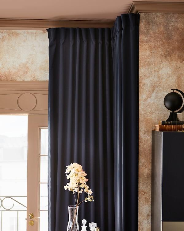 Prostorija s MAJGULL tamnoplavim zavesama za zamračivanje, povučenim tako da ulazi svetlo, uz grančicu s cvećem u staklenoj vazi.