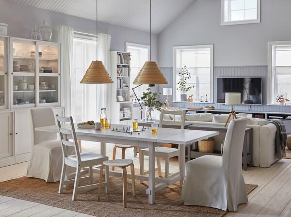 Просторная и светлая столовая со смежной гостиной. Обеденный стол раздвинут, а табуреты обеспечивают больше сидячих мест.