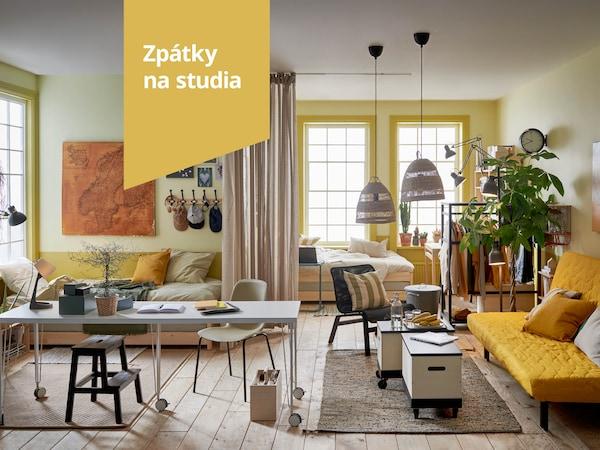 Prostorný pokoj se světle žlutými stěnami, žlutou pohovkou NYHAMN a odkládacími stolky na kolečkách RÅVAROR.