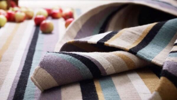 Proužkovaný koberec – fialová, žlutá, modrá, bílá, černá.
