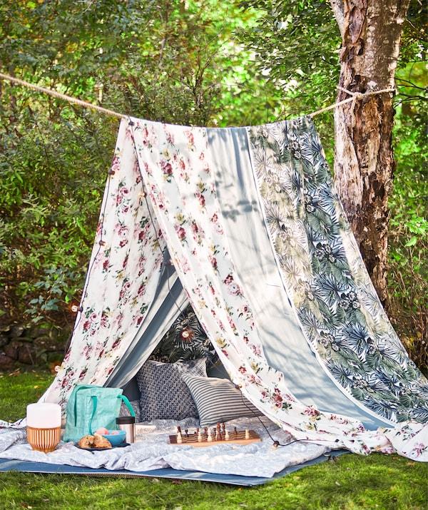 Provaz natažený mezi stromy, barevný textil EMMIE ROS jako letní stan na piknik