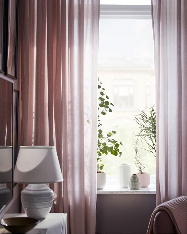 Prozori u dnevnoj sobi, s HANNALILL zavesama u roze nijansi koje filtriraju svetlost, i nekoliko biljaka i saksija na simsu.