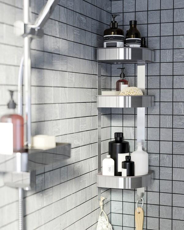 Prysznic z szarymi płytkami i półka narożna ze stali nierdzewnej, na której stoją żele pod prysznic, szampony i inne akcesoria.