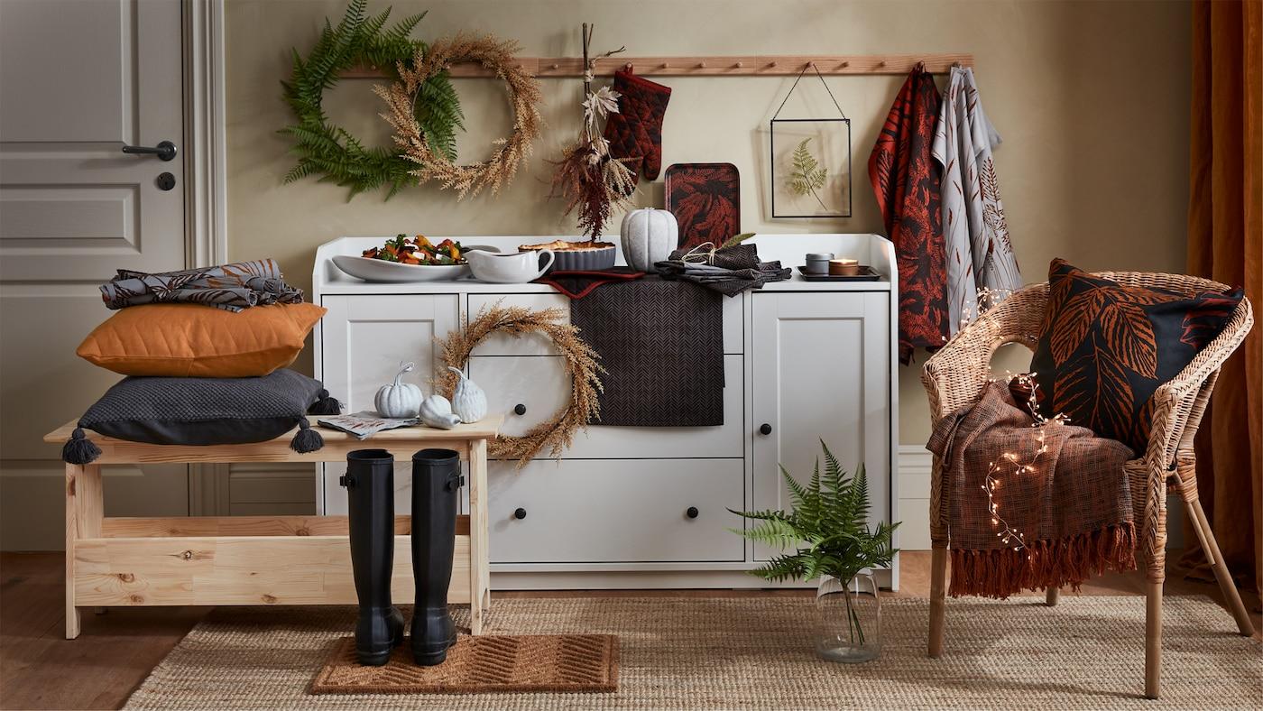 Przedmioty z kolekcji HÖSTKVÄLL, takie jak poduszka, narzuta, forma z ciastem, serwetki z tkaniny i inne obok kredensu HAUGA lub na nim.
