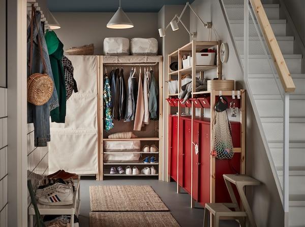 Przedpokój z czerwonymi szafkami, białymi lampami, dwoma dywanami z juty, białymi półkami na buty i regałami w kolorze beżowym i z drewna sosnowego.