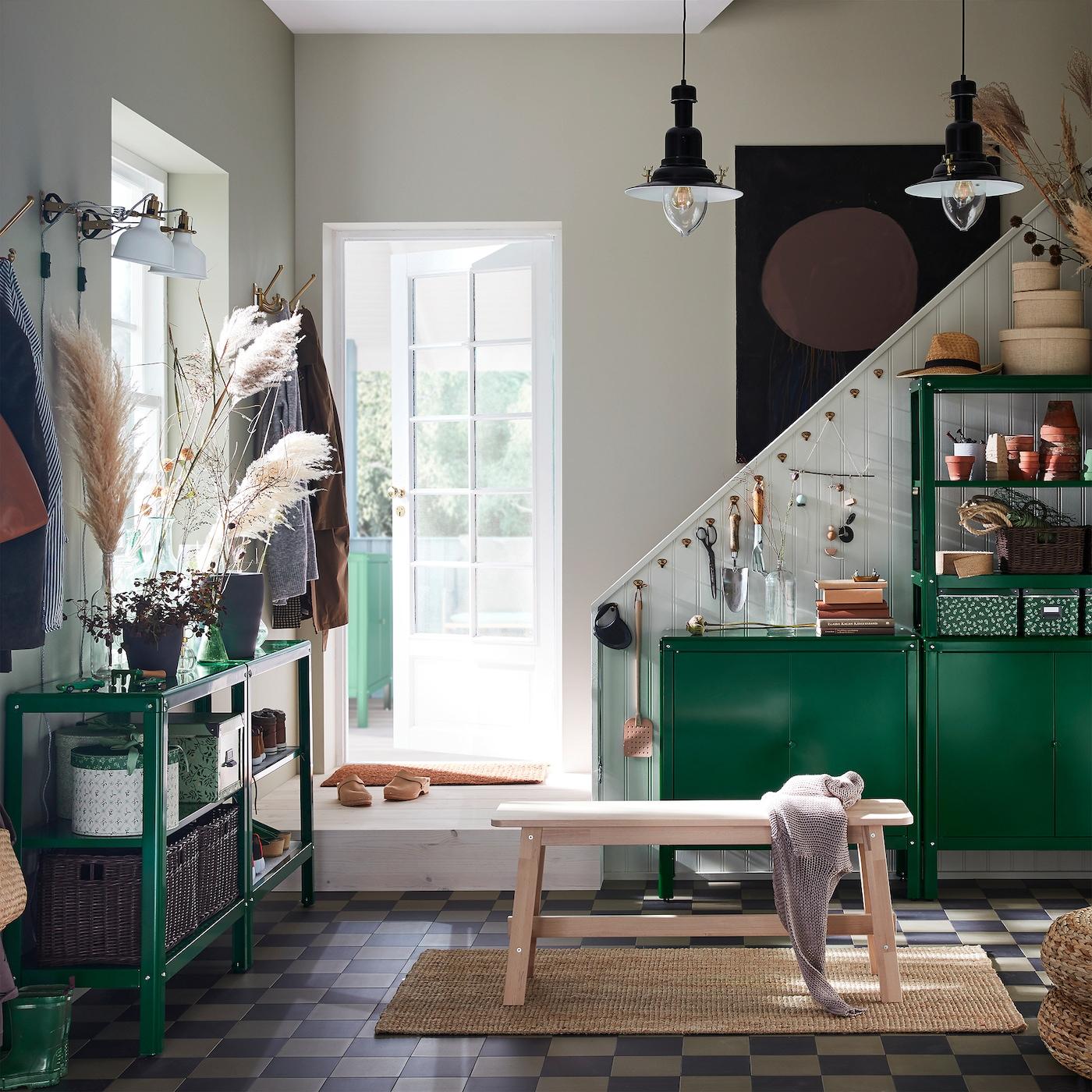 Przedpokój z zielonymi regałami i szafkami KOLBJÖRN, brzozową ławą, jutowym dywanem i dwiema czarnymi lampami wiszącymi.