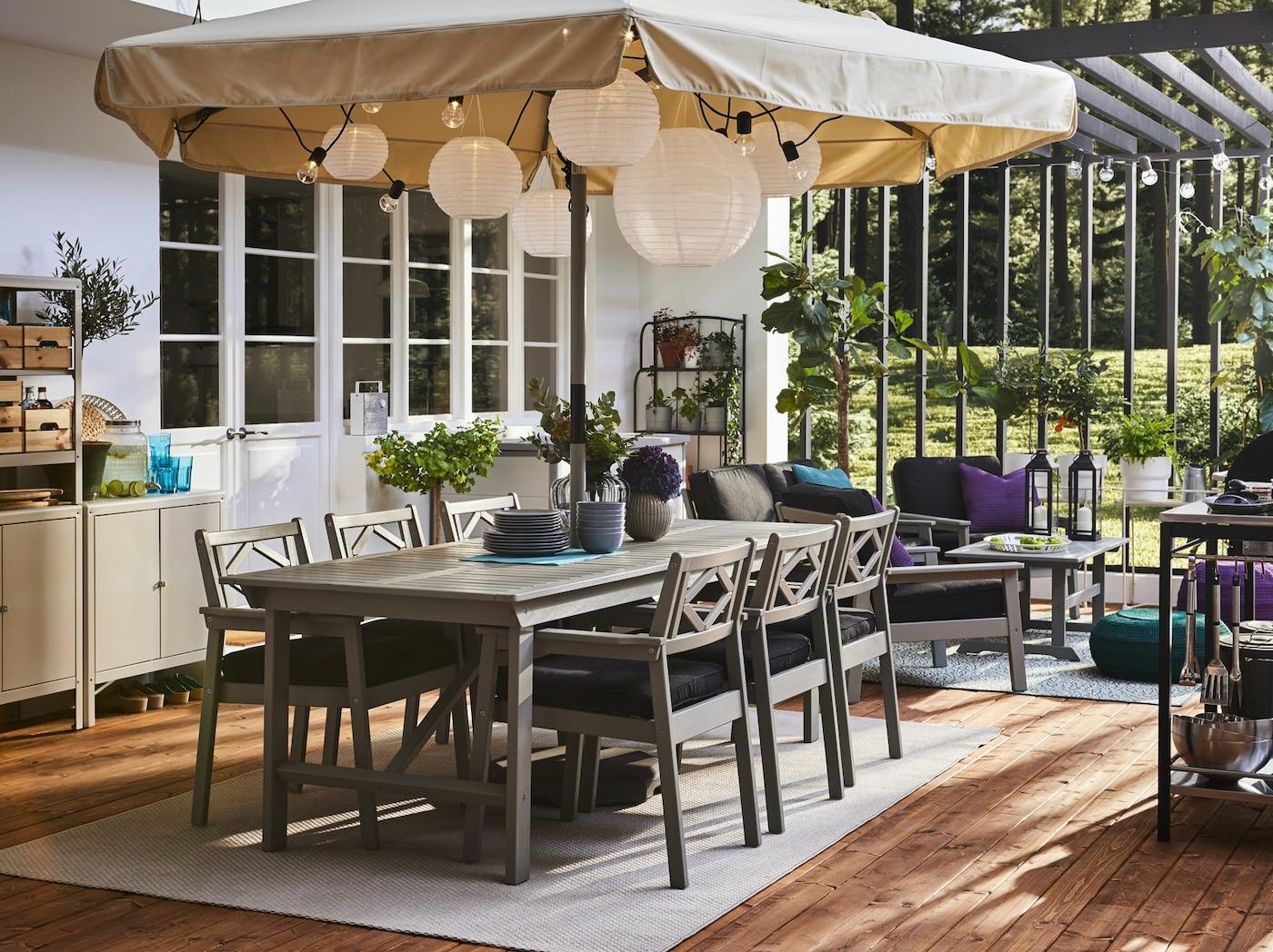Przestronne patio z szarym stołem i krzesłami z podłokietnikami, dużym parasolem, okrągłymi lampami wiszącymi i drewnianą podłogą.