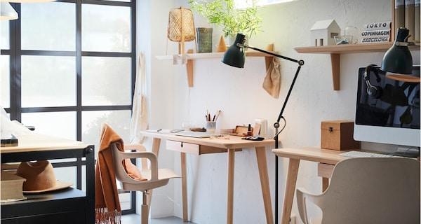 Przestrzeń do pracy z dwoma czarnymi wózkami z drewnianymi blatami BROR, dwiema białymi lampami wiszącymi i długim czarnym regałem.