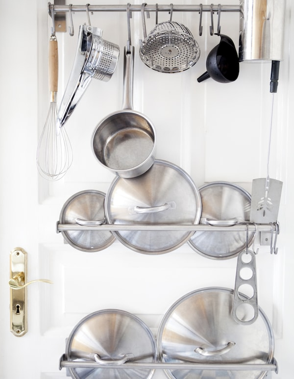 Przybory kuchenne i pokrywki na drążkach na drzwiach.