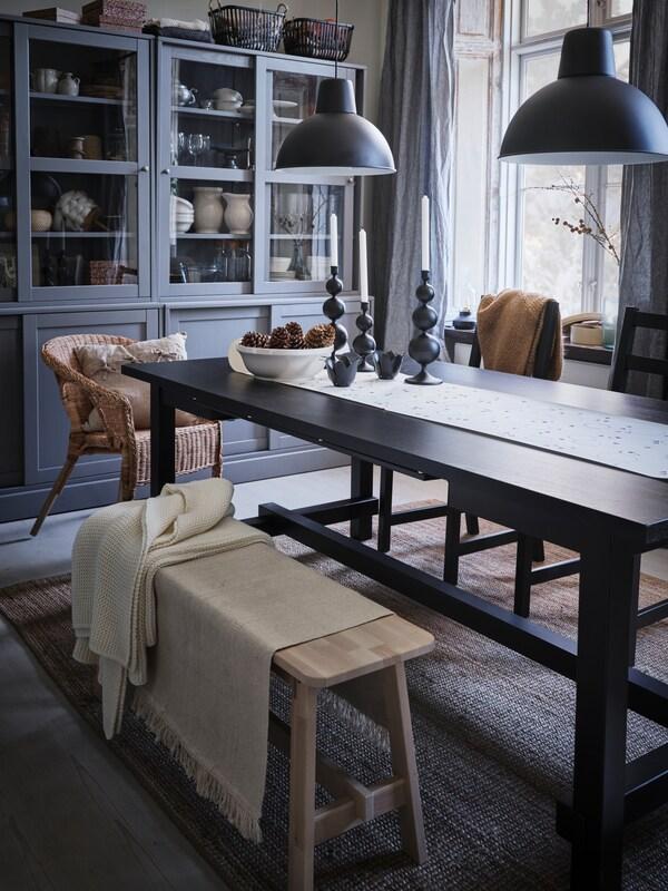 Przygotowany na świąteczny posiłek czarny, rozkładany stół NORDVIKEN ustawiony w pomalowanym na jasne kolory pomieszczeniu.