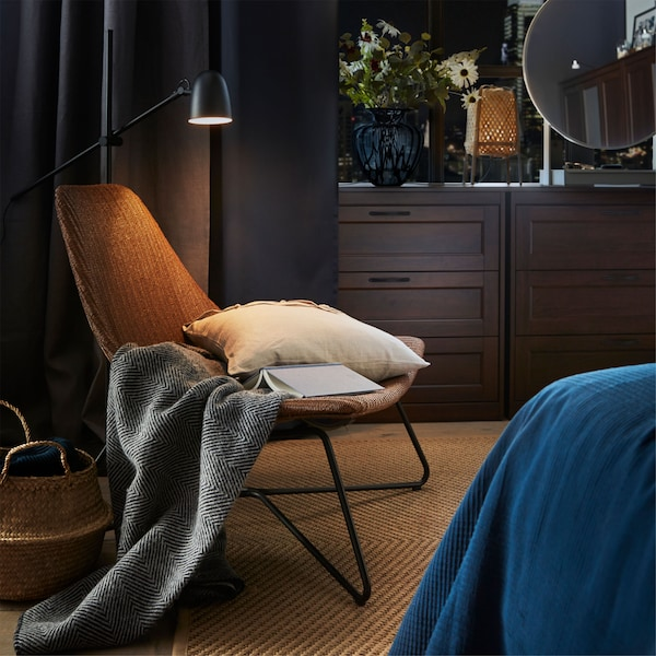 Przytulny kącik do czytania w sypialni z ciemnobrązowym/czarnym fotelem IKEA RÅDVIKEN i czarną lampą podłogową do czytania SKURUP.