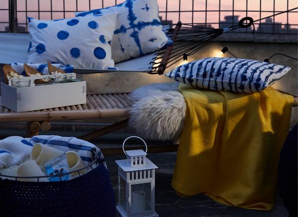 Pufe oco, virado ao contrário, com têxteis e velas LED, junto a uma mesa de centro e uma rede, ambas com têxteis em cima.