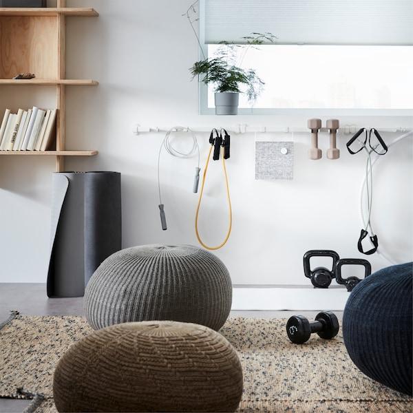 Pufes SANDARED espalhados numa área de descontração de um escritório e calha VAJERT, em branco, fixada com equipamento de desporto.
