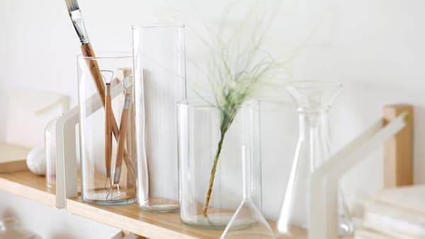 Puinen seinähylly jolla on erilaisia lasisia purkkeja.