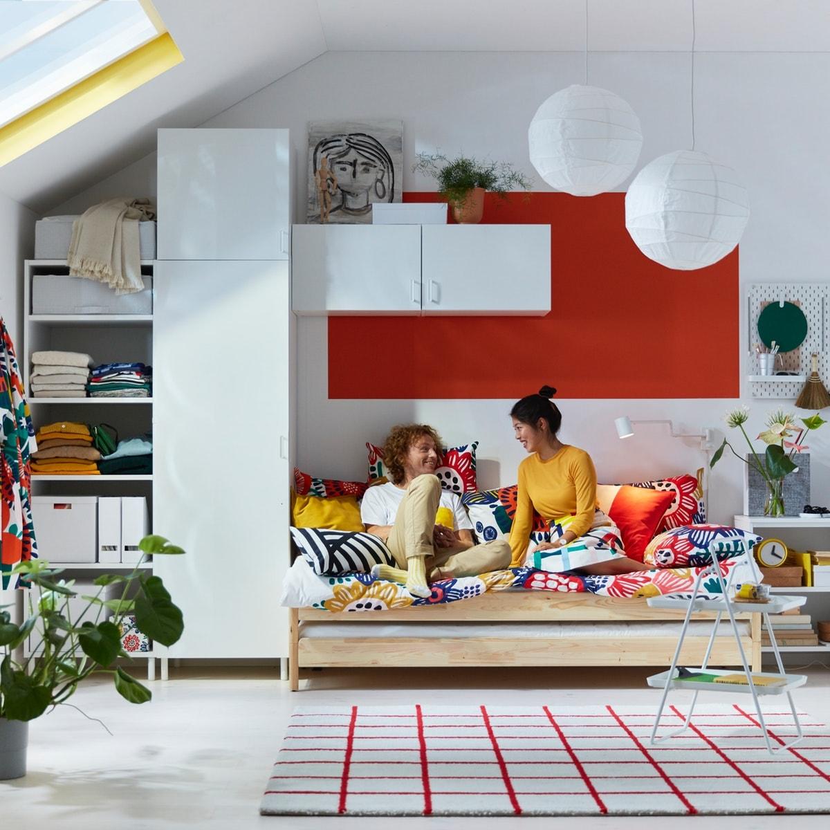Puinen UTÅKER-sänky, värikkäät pussilakanat ja punavalkoinen graafinen matto.