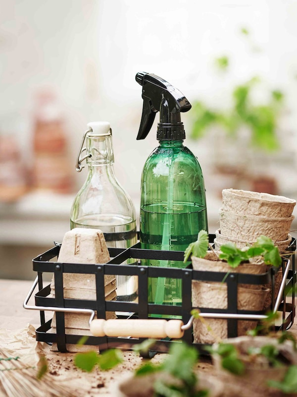 Pulverizador verde e garrafa de vidro arrumados num cesto metálico.