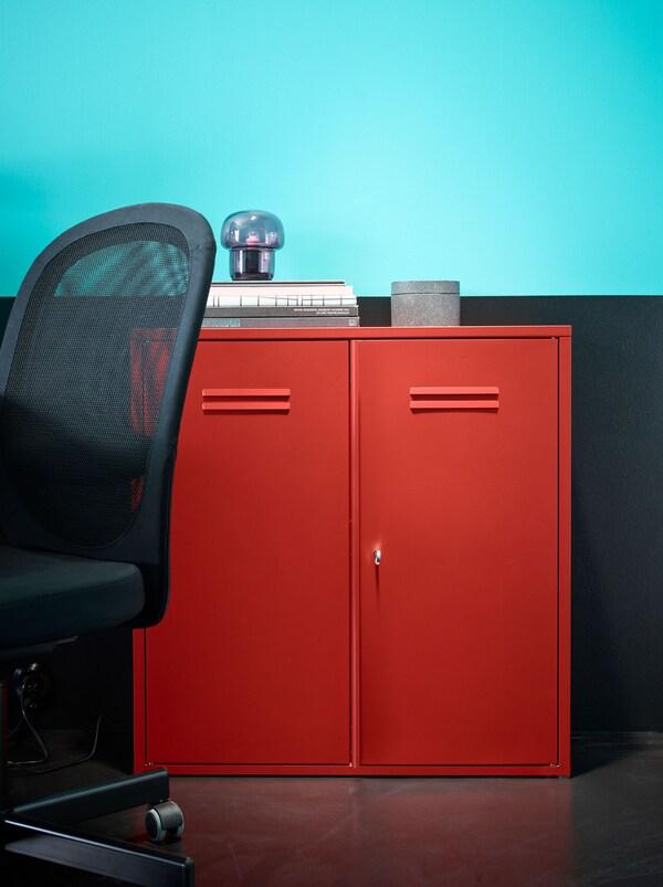 Punainen IVAR-kaappi turkoosi/mustan seinän edessä. Musta FLINTAN-tuoli on kaapin vieressä.