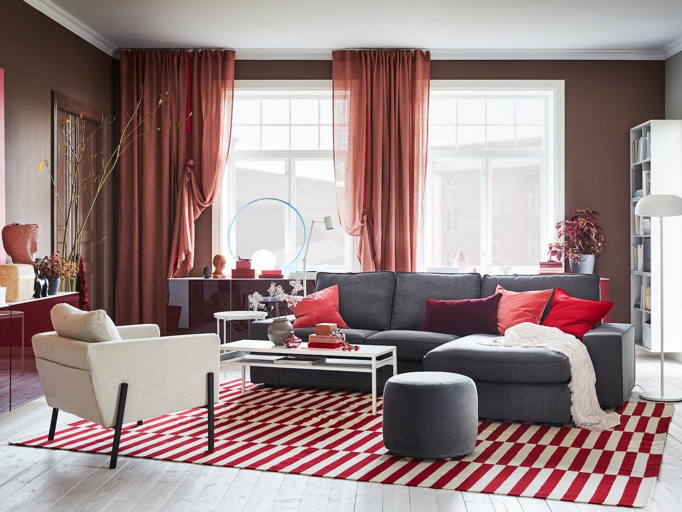 Punasävyinen olohuone, jossa suuri tummanharmaa sohva.
