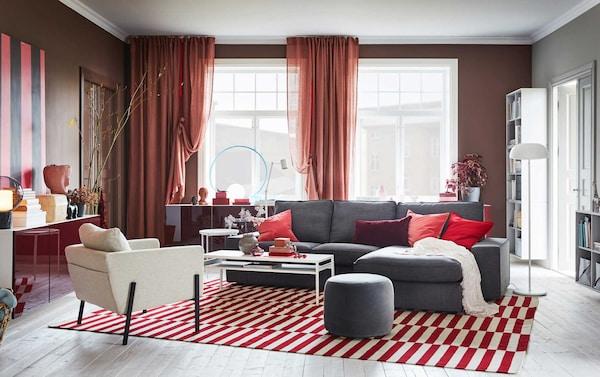 Punasävyisessä huoneessa tummanharmaa sohva punavalkoisella matolla.