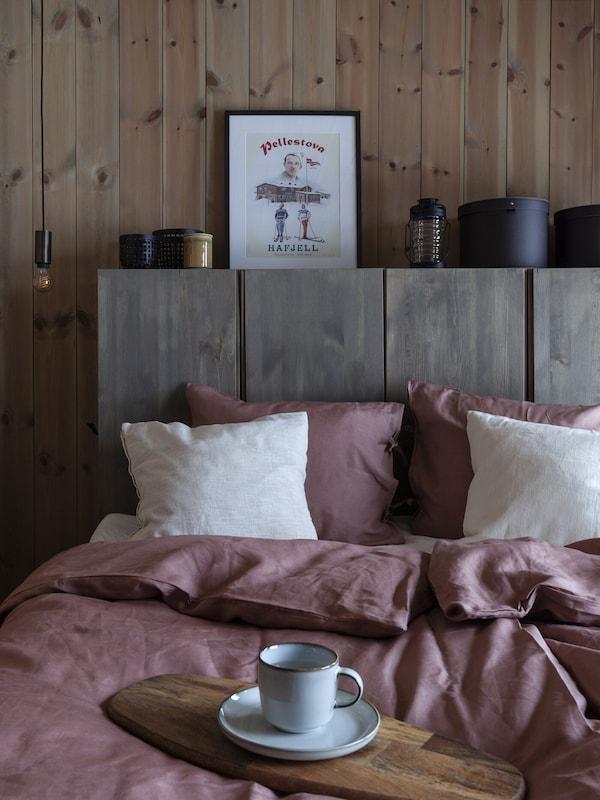 Punertavat lakanat sängyllä. Sängyn takana tummaksi petsattu IVAR-kaappi.