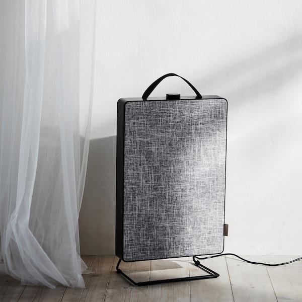Purificateur d'air FÖRNUFTIG gris clair sur un plancher en bois, dans une chambre à coucher ensoleillée.