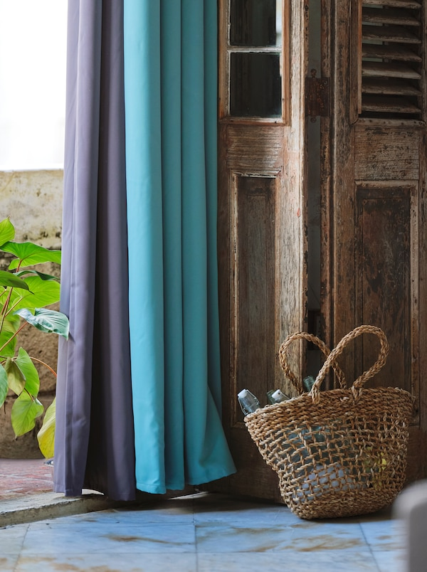 Purple and turquoise block out curtains hanging against an open, wooden door with a woven basket placed next to it.
