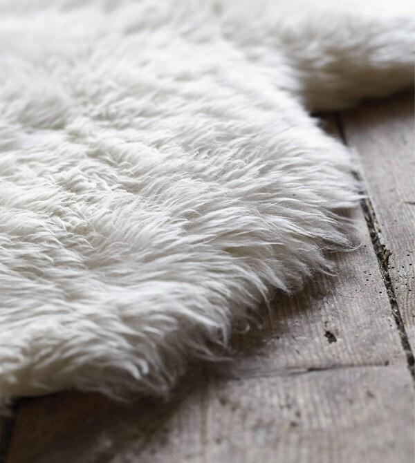 Пушистая овечья шкура ЛУДДЕ на деревянном полу