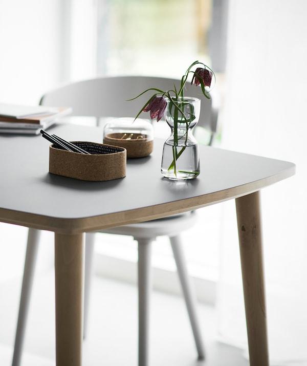 Puupöydällä on pieni kukkamaljakko.
