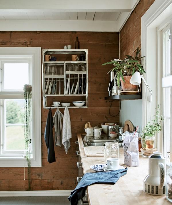 Puutyötaso puupaneloidussa keittiössä, jossa on avoin säilytystila, mukaan lukien seinälle asennettu teollisuuskaappi ja astiat.