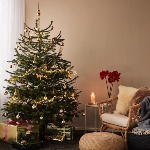 Pyntad julgran u rum med gröna väggar.