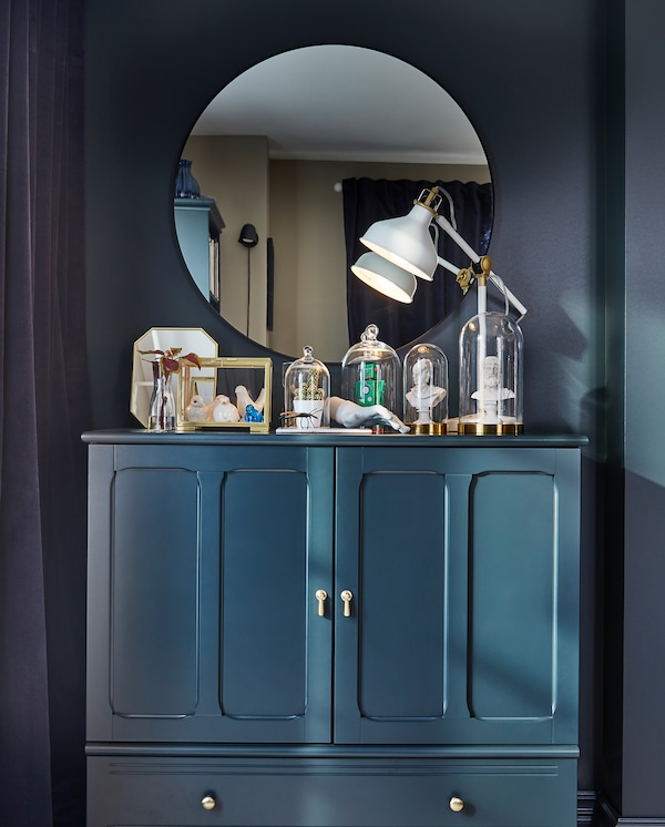 Pyöreä seinäpeili, tumman sinivihreä kaappi ja koriste-esineitä pienissä vitriineissä ja lasikupujen alla.